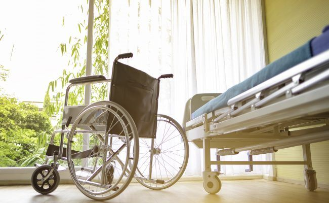 wheel chair and the Patient's bed in the hospital, Empty wheelchair and Patient's bed standing in hospital with sunlight background.